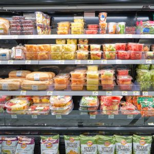 Grocery store refrigerated aisle with packaged fruits and sandwiches