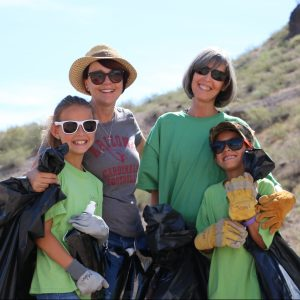 Teachers and students smile while collecting trash at A Mountain