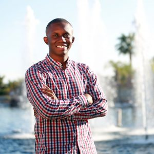 Sustainability student Jeffrey smiling in front of fountains and palm trees