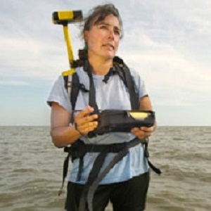 Woman with equipment wearing backpack in front of ocean