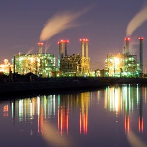 Illuminated power plant at night, its reflection in nearby water