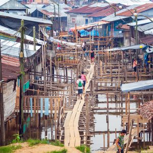 A wooden walkway winds through a slum built over water