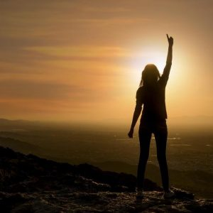 Woman standing on mountain at sunset pointing toward the sky