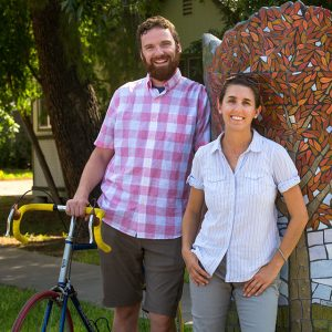 Tall, smiling man with bike next to smiling young woman outdoors