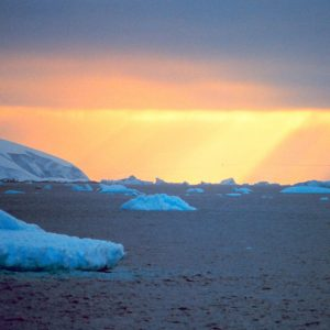 Sun setting over ice sheets and ocean