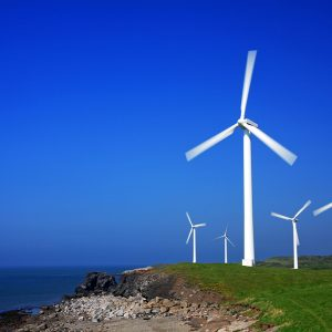 Turbines on a green, open meadow overlooking ocean