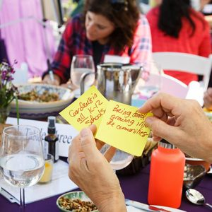 Diners take notes while eating colorful meal outdoors