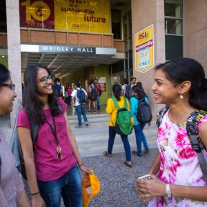 Three female students talk and laugh outside of ASU's Wrigley Hall.