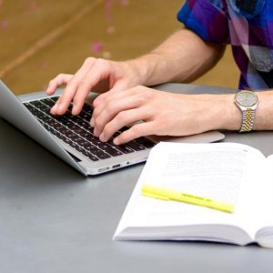 Hands type at a laptop, with a notebook and highlighter in the foreground