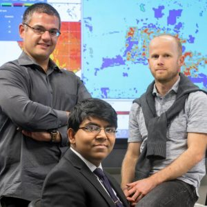 Georgescu and another researcher pose in front of climate models with 16-year-old computer whiz Gupta