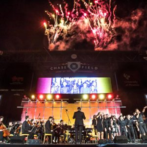 Fireworks light up the sky over a band onstage at a baseball park