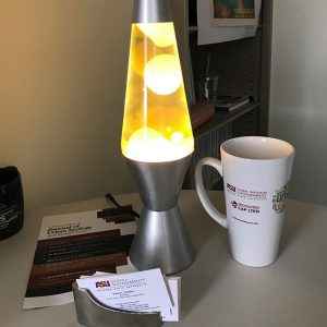 Yellow lava lamp on a table along with a mug and business cards
