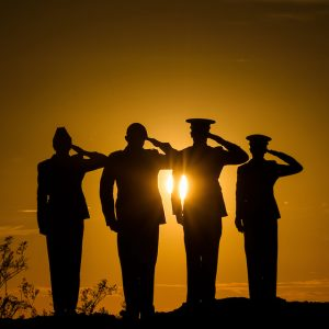Soldiers saluting at sunset