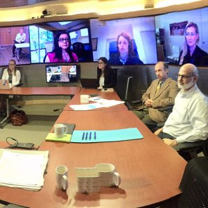 Scientists gather around table and behind them multiple screens showing other scientists videoconferencing