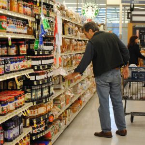Man in supermarket aisle reaching out to grab a product on the shelf