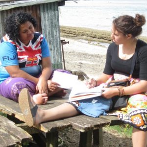 An SOS students sits, interviewing a Fijian woman, also seated.
