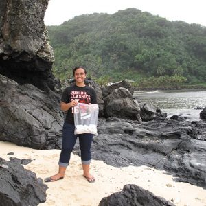 Female student standing with a bag containing pieces of plastic by sea shore