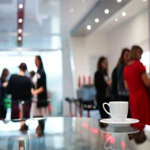White coffee cup over shiny conference table with blurred view of women gathering in the background