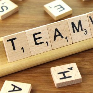 "Close up of Scrabble wood pieces on stand that read ""TEAM"""