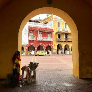 Thick yellow wall with arched doorway facing street with colonial buildings