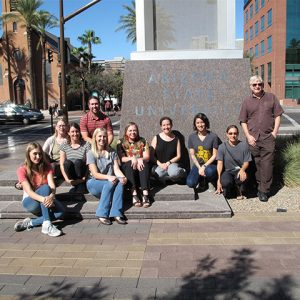 Participants group photo sitting around ASU welcoming statue
