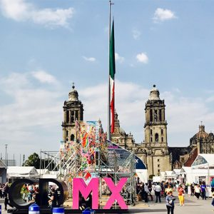 Socalo plaza in Mexico City with cathedral on the back and people walking around vendor tents