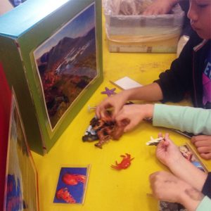 Close up of kids hands playing with animal figurines