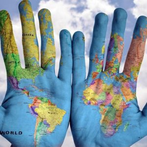 Two hands next to each other showing painted world map on palms