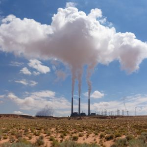 Three smoke stacks at a power plant with billowing smoke in northern Arizona