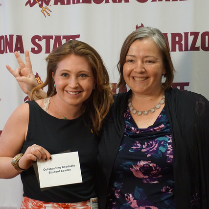 Student Zoe Stein holds an ASU Pitchfork Award for Outstanding Graduate Student Leader. She is posing with Katie Ulmer, her academic advisor.