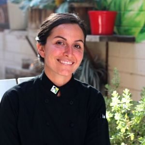 Chef Danielle Leoni wearing a chef's coat and smiling