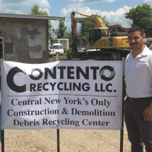 Anthony Contento stands near a sign for his business, Contento Recycling