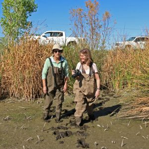 Two researchers stand in mud and hold cameras at Tres Rios, Arizona