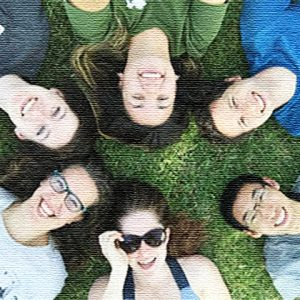 Students smiling laying on grass making a circle with their heads