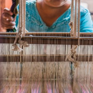 Woman weaves at traditional loom
