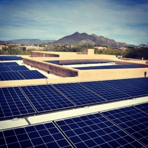 Solar panels on building with desert mountains in background