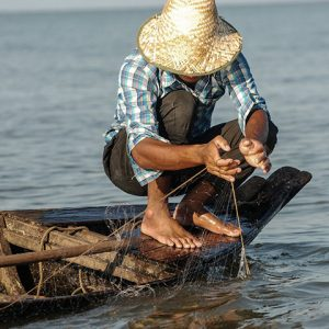 Fisherman in Mekong stands on edge of canoe to prep fishing gear