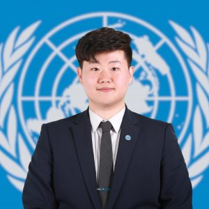Sustainability student Junkee Ahn in suit standing in front of UN seal