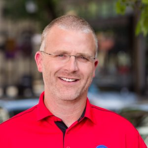 Smiling man with glasses and red collared shirt