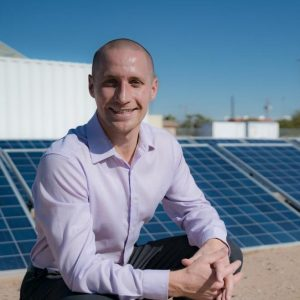 man in collared shirt posing in front of solar panels