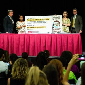 ASU President Crow accepts a large placard recognizing that ASU is the largest fair trade university in the U.S.