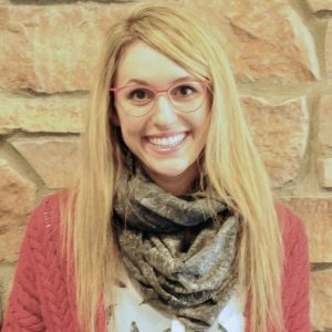 Blond woman wearing a scarf and glasses smiling