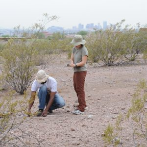 2 people making measurements in desert with city skyline in the background