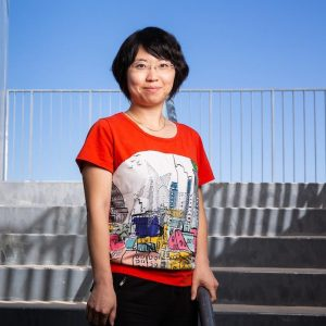 Woman with black hair and red shirt standing on stairs