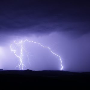 lightning over mountains with purple sky