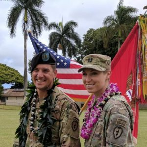 Uniformed US Army couple wearing leis and smiling in front of US flag