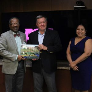 Michael Crow stands with visitors from Guyana