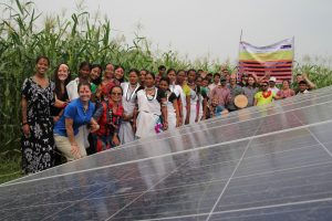 Students and Nepali community stand next to solar panels