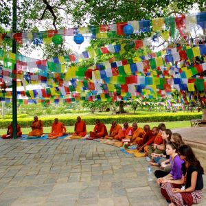 Students sit in a circle with monks under colorful flags