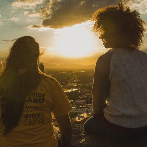 Two women sitting on mountainside at sunset